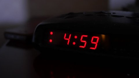 A man turns off the alarm when a digital alarm clock turns to five o'clock