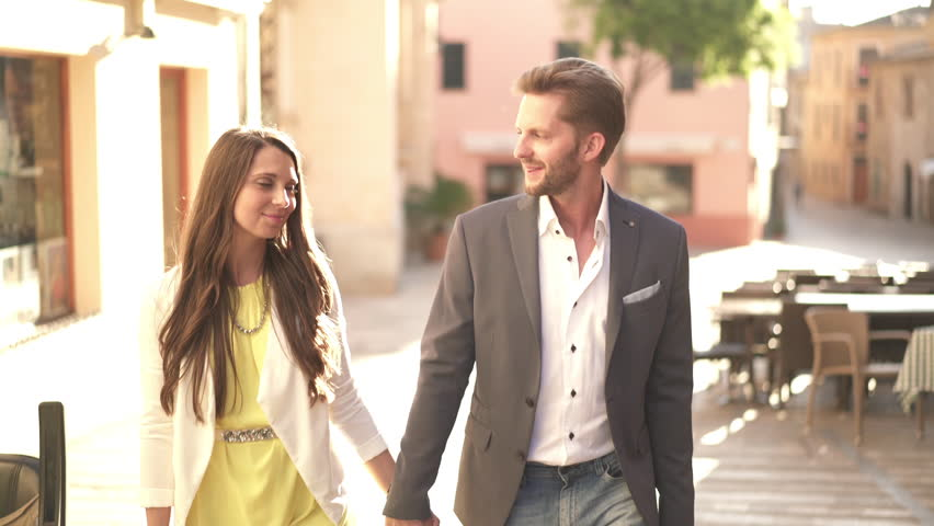 4k footage, young couple in love walking through old town with little restaurants