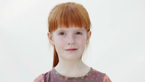 Little redheaded girl is giving a wink, white background, close up
