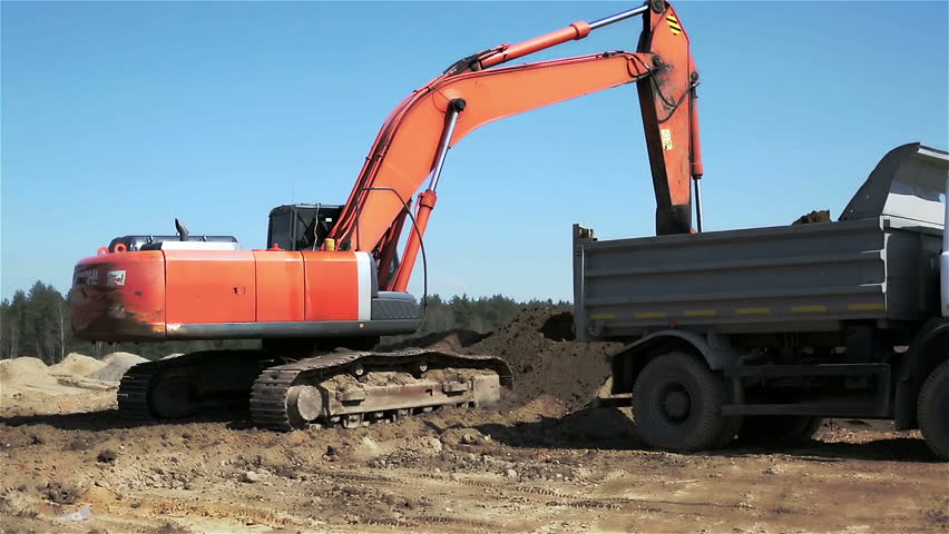 Tractor bucket is filling a truck body. Orange hydraulic crane with bucket is on a background of blue sky. A excavator and truck are loading soil.
