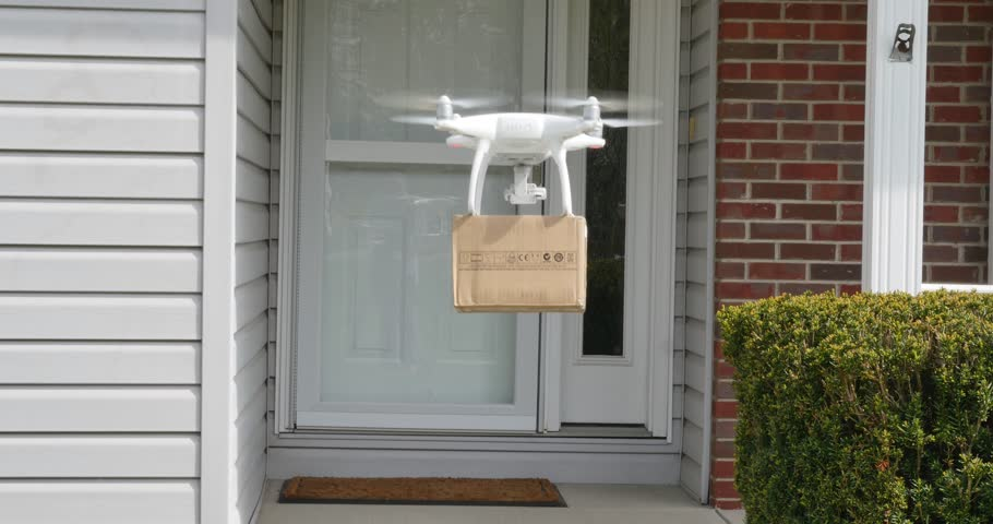 A small drone delivers a package to a residence.