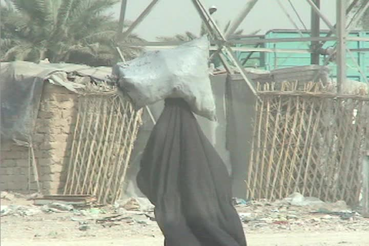 A veiled Muslim woman walks down a street in rural Iraq carrying a bag of goods on her head.