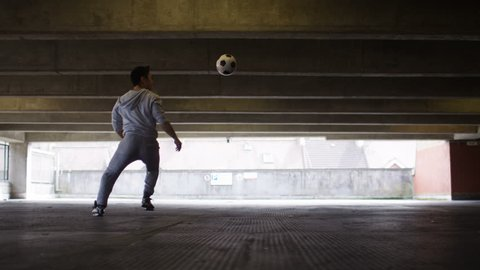 4K Football player doing kick up tricks in an urban city environment, in slow motion