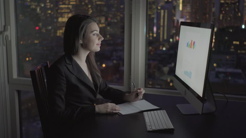 businesswomen working on computer desk in modern office at night analyzing financial growth of the company. charts diagram calculation infographic background