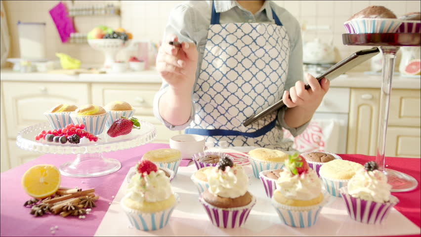 Woman Decorating Cupcakes woman decorating cup-cakes with sprinkling and berries / shot of