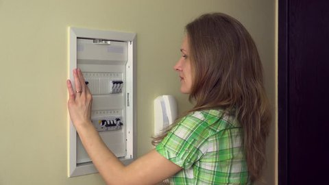 woman turning on light-switch at power control panel and smiling at camera at home. Static closeup shot.