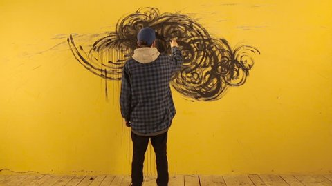 Artist paints the abstract ornament with black brush on yellow wall