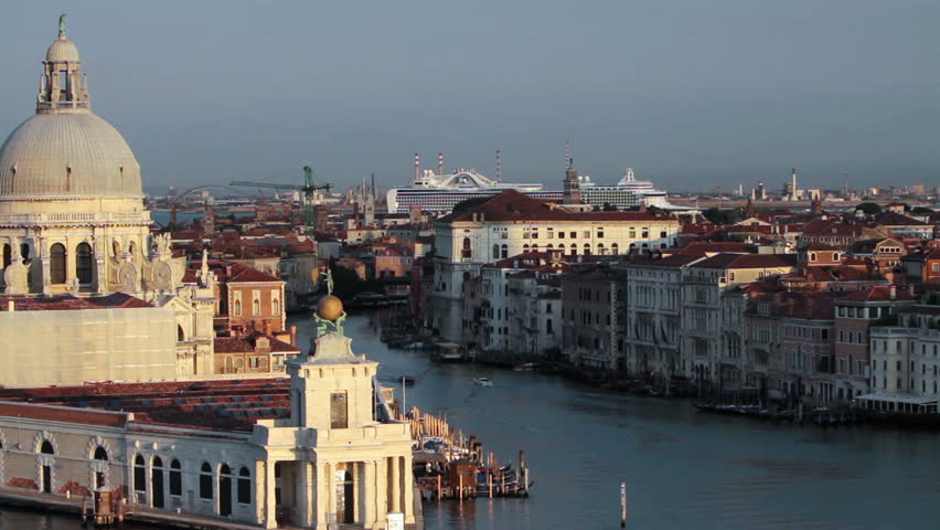 Venice Italy canal and lagoon passing by the Santa Maria delle Salute basilica cathedral. Early morning light. Cruise ship in distance at marina port. Video capture from moving ship at high angle