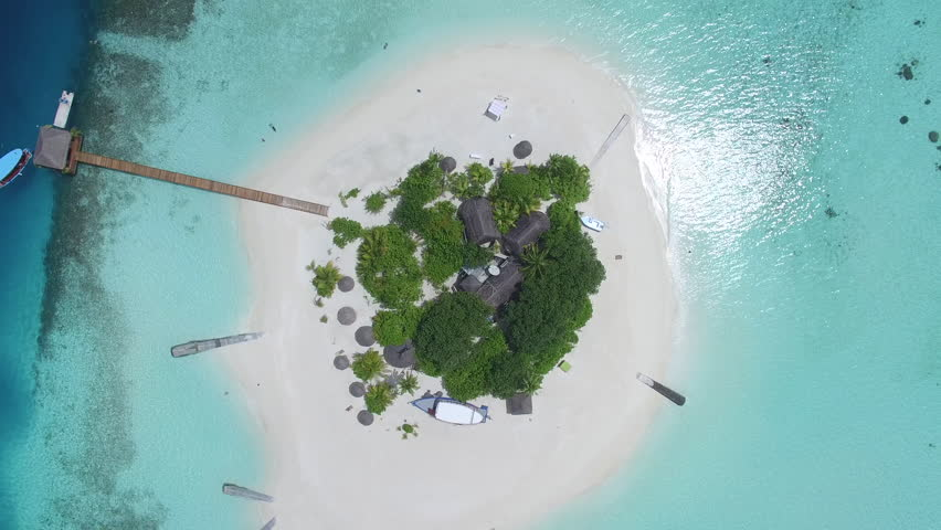 Aerial shot of a small tropical island in Maldives island, 2015. Palms and jetty on the sandbank. Camera rise up. | Shutterstock HD Video #16501033