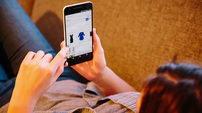 ZAGREB - CROATIA - FEBRUARY 7, 2016: Girl online shopping on smartphone through eBay web page. eBay Inc. is an American multinational corporation and e-commerce company