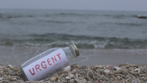 Urgent slogan written on paper as a message in a bottle washed ashore