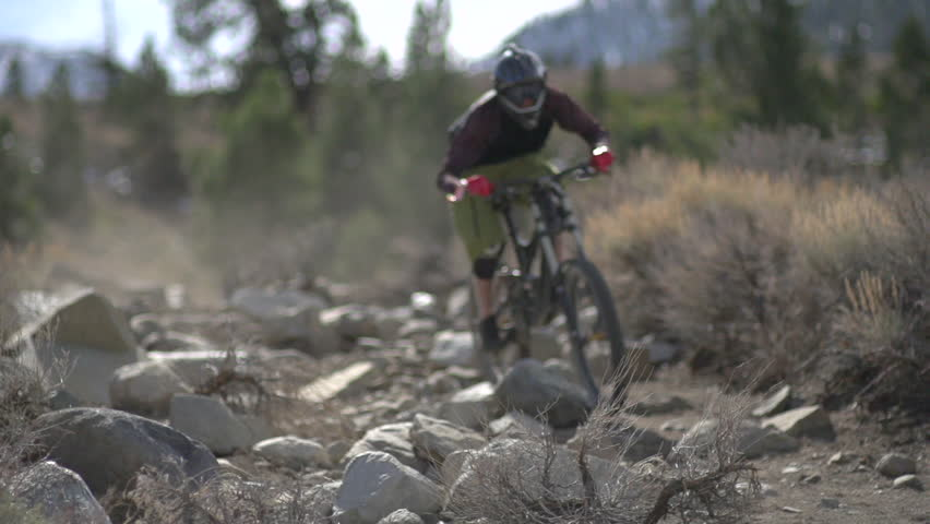A young man mountain biking on scenic trail in the mountains. - Super Slow Motion - Model Released - 1920x1080 - Full HD - filmed at 240 fps