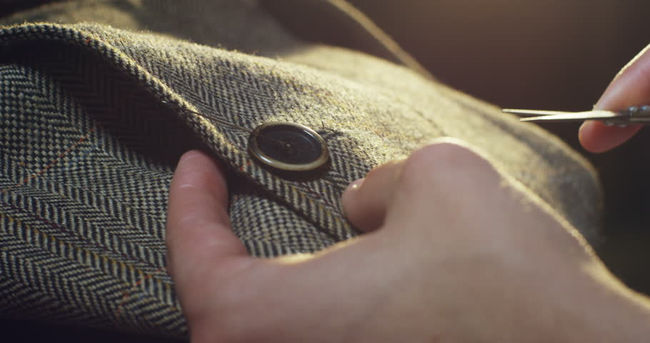 Slow motion of a hand of a young tailor who cuts the thread to sew in her studio with tailor tools to be able to sew the dress