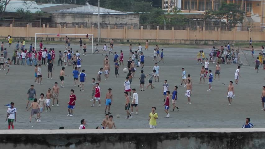 Boys in a school yard playing soccer.