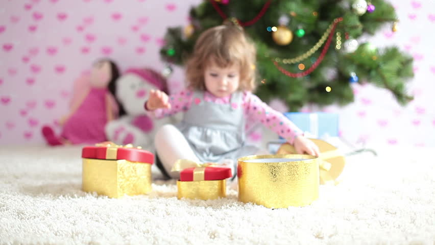 Baby girl is preparing a Christmas gifts and looking at camera
