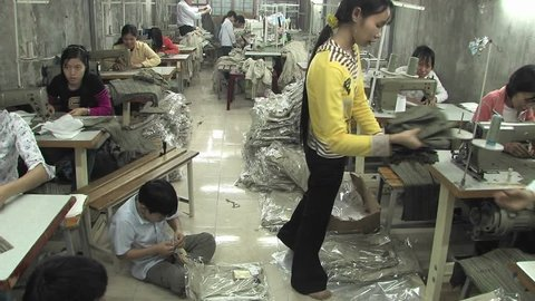 CHINA - CIRCA 2009: Women in a small factory sewing clothes in China circa 2009