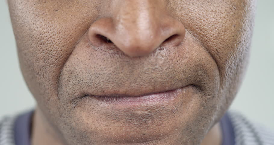 Male African-American strongly angry. His lips pressed tightly together. Breathing frequent. He barely restrains himself/The Man Strongly Displeased