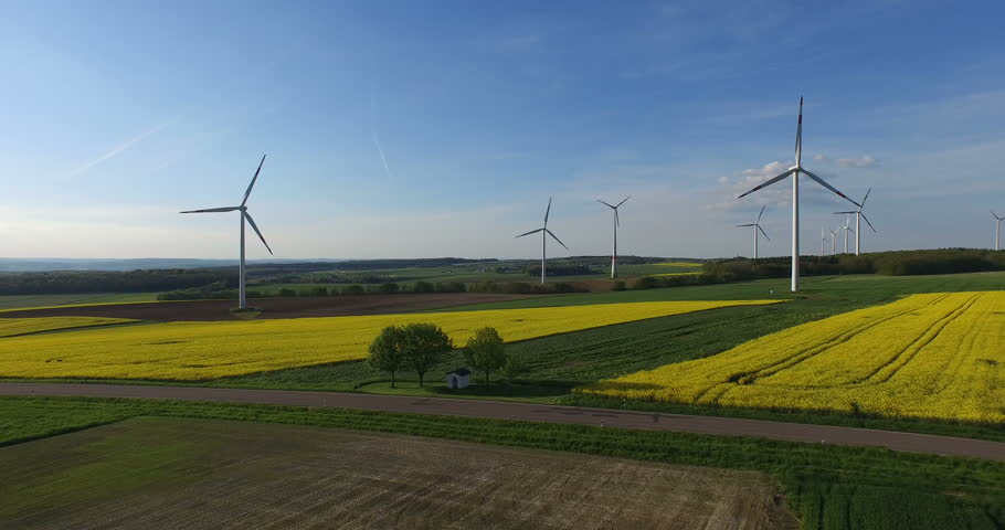 4K aerial video of the wind turbines and rape field.