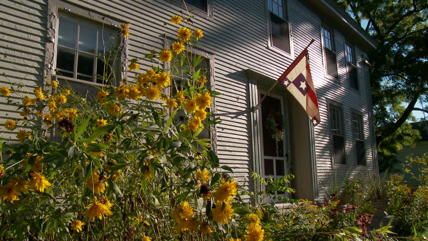 Flowers and flag outside white household