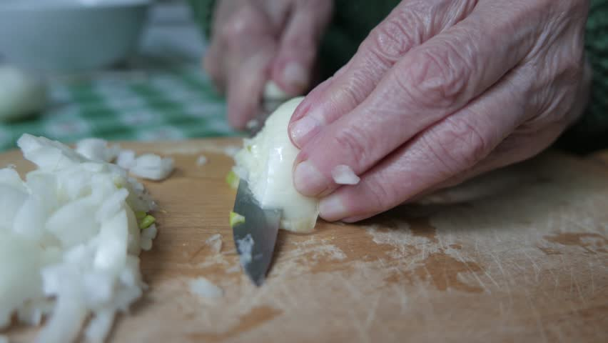 Old wrinkled hands chopping some onions. #16641229