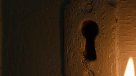 Skeleton key inserted in door by candlelight