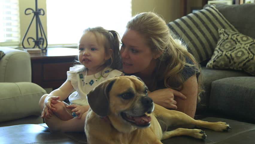 Happy smiling mom gets cute toddler who is busy watching TV to smile and blow a kiss while tired dog rests by her side..