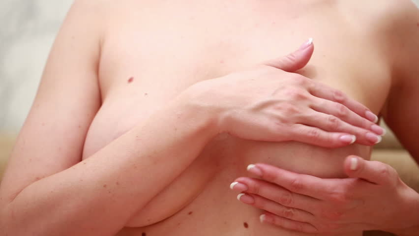 Examining breasts. Close-up of young shirtless woman examining her breasts while. Isolated white background   Shutterstock HD Video #16650829