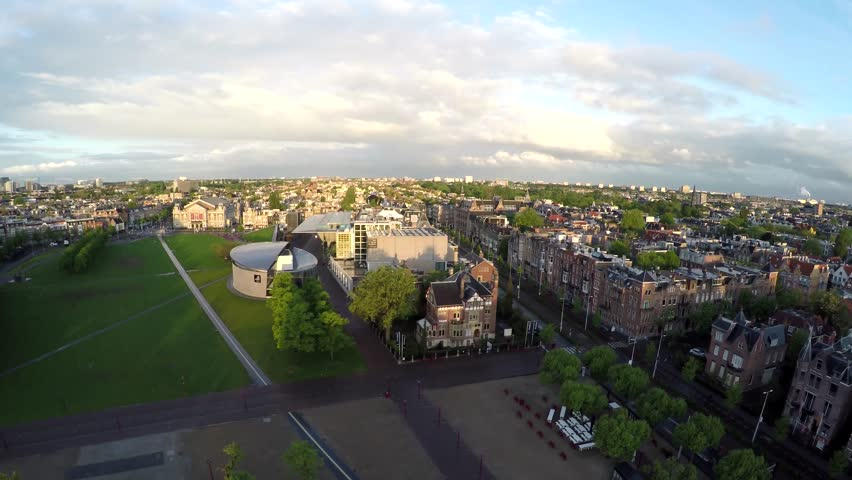 Aerial Amsterdam Museumplein flying backwards from Van Gogh Museum an art museum in Holland dedicated to works of Vincent van Gogh and Concertgebouw in background both popular tourist attractions 4k