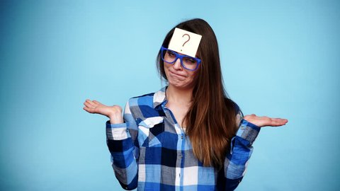 Woman confused thinking seeks a solution, paper card with question mark on her head. Doubtful young female studio shot blue background. 4K ProRes HQ codec