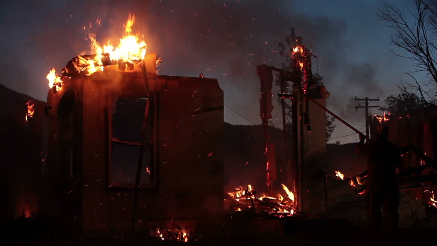 Fireman working on a house fire after dark at night, pushing burning wall down. Flames consume entire home.