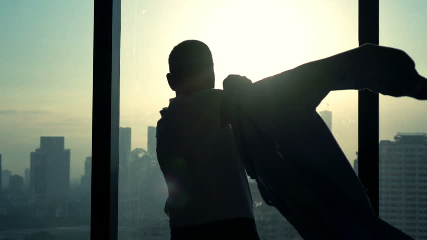 Man putting on shirt standing by window at home, slow motion    Shutterstock HD Video #16666363