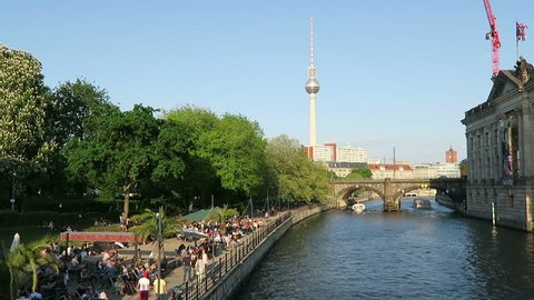 BERLIN, BERLIN/ GERMANY MAY 09 2016: People sitting in the evening sun at Spree river cafe in Berlin. In background tv tower of Alexanderplatz. Tourist boat comes along