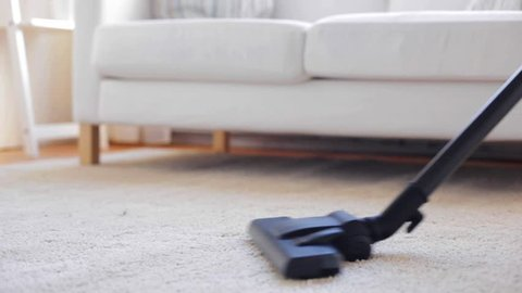 people, housework and housekeeping concept - woman with vacuum cleaner cleaning carpet at home