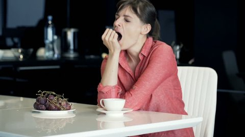 Sleepy, young woman yawning and drink by table in the kitchen