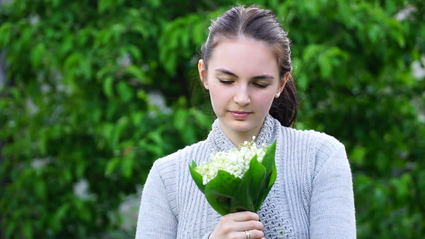 footage woman is smelling the lily of the valley in the garden. HD video