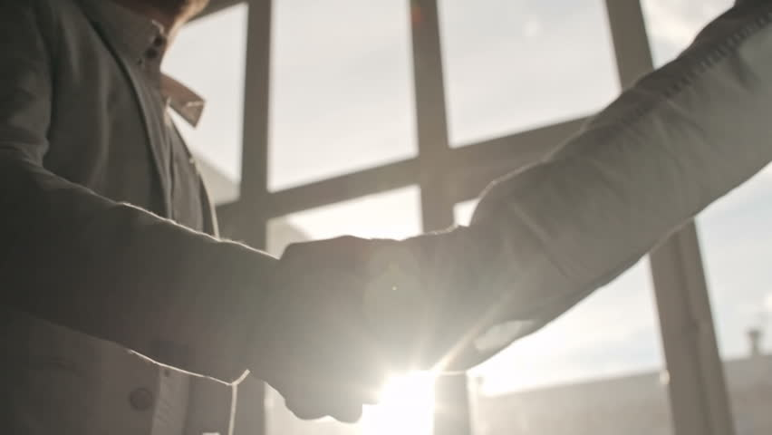 Two businessmen shaking hands to greet each other and talking in office, backlit shot on Sony NEX 700 | Shutterstock HD Video #16739899