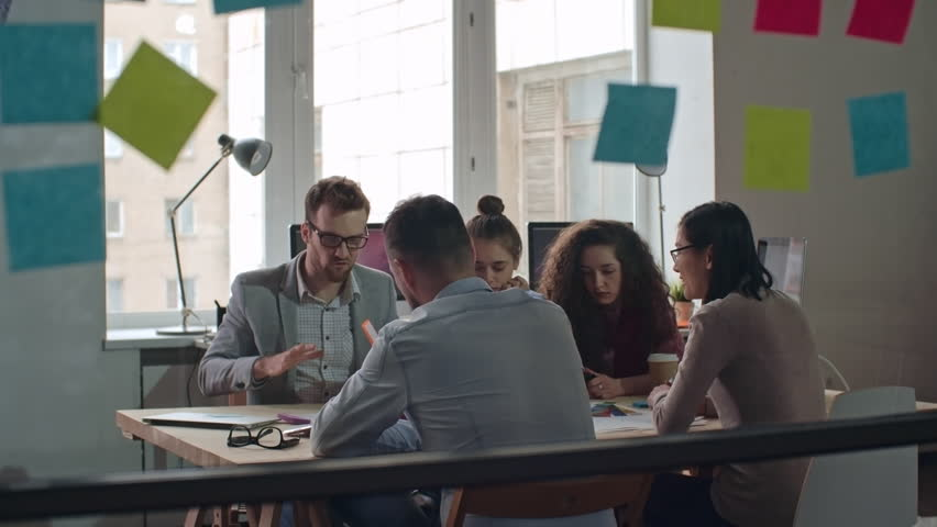 Creative young business team sitting at table and brainstorming to generate ideas in meeting, team leader explaining his idea, shot on Sony NEX 700 + Odyssey 7Q | Shutterstock HD Video #16740481