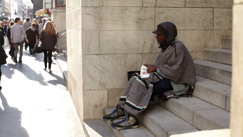 NEW YORK CITY, NY - NOVEMBER 25: Homeless man sitting on steps asking for money during Black Friday shopping spree on November 25, 2011 in New York City, New York.