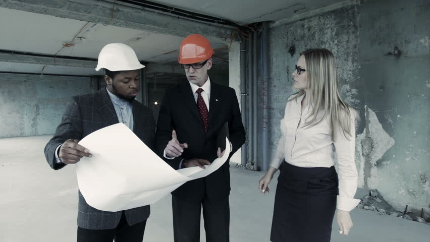 The development group of a project standing and discussing the men woman in suit and helmet discuss blueprint communicate with buyer chief engineer malvernweather Choice Image