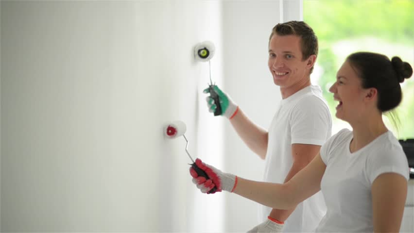 Young couple decorate their new apartment. Young husband and wife are painting the wall. Beautiful couple making repairs in their new flat.