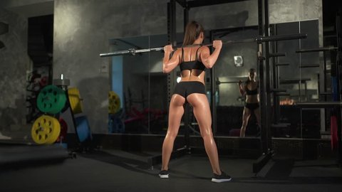 beautiful sporty woman doing squat workout in gym