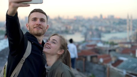 happy couple making selfie on a rooftop slow motion