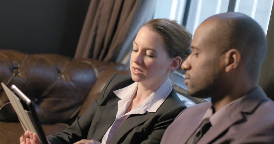 African American business man and Caucasian business woman looking at work on a tablet computer while sitting on a leather sofa in a relaxed indoor setting.  Slow motion side view recorded at 60fps. | Shutterstock HD Video #16854949