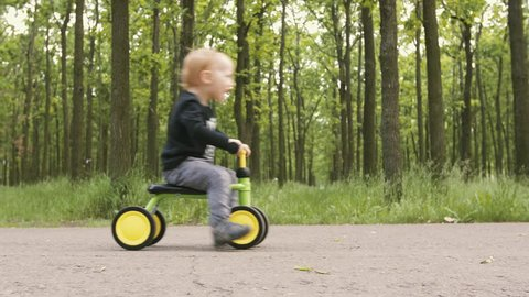 Dolly shot of little boy riding small bike without pedals on road in the park. Happy child on bicycle having fun outdoors in park. Active kid playing, cycling and spending family time.