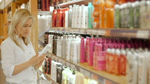 Beautiful Woman Choosing Body Care Products In Supermarket