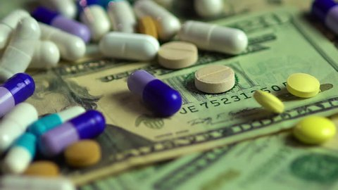 Pills falling on dollar banknotes, expensive medication, pharmaceutical business. Investment in hospitals, high price treatment, medical consumerism. Drugs development and production, market financing