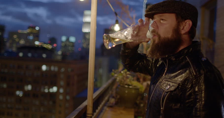 Bearded man in leather jacket and flat cap drinking beer alone on balcony at night in Downtown Los Angeles, California.  Recorded in slow motion at 60fps.
