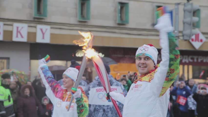 SAINT PETERSBURG, RUSSIA - OCTOBER 27, 2013: Relay race Sochi Olympic flame in Saint Petersburg. October 2013. Torchbearers transfer fire. Wave hands. Crowd of people. Olympic uniform