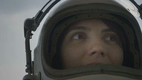 Close up shot of astronaut woman with the helmet visor up relaxing and breathing deep.