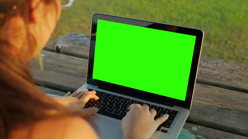 Young woman using a notebook computer with a key green screen. | Shutterstock HD Video #16990588
